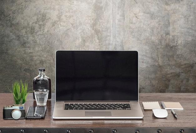 Mockup laptop with black screen and supplise on wooden table.