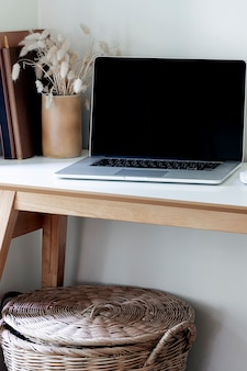 Mockup laptop with black screen on wooden table.