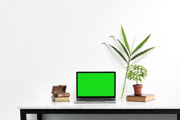 Макет ноутбук с зеленым экраном на мраморный стол с листьями природы положить на стол