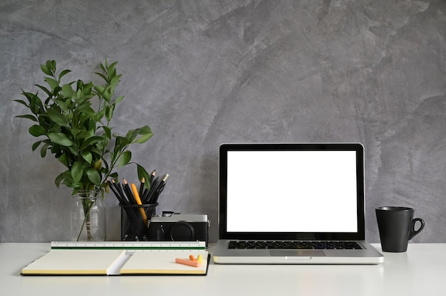 Mockup laptop on workspace with office supplies and loft wall
