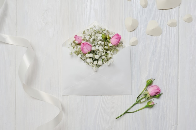 Mockup letter with flowers rose for st. valentines day in rustic style with place for your text, flat lay top view