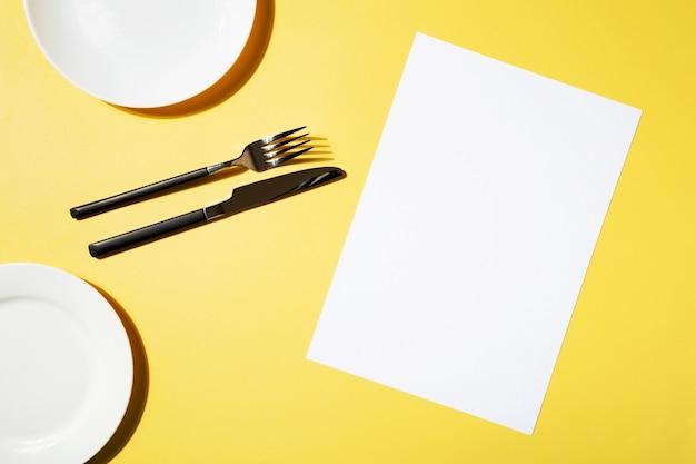 モックアップメニューレストラン、フォークとナイフ、黄色の背景に空のプレート。上面図。コピースペース