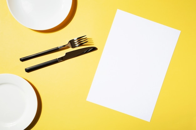 Mockup menu restaurant, fork and knife, empty plate on yellow background. top view. copy space