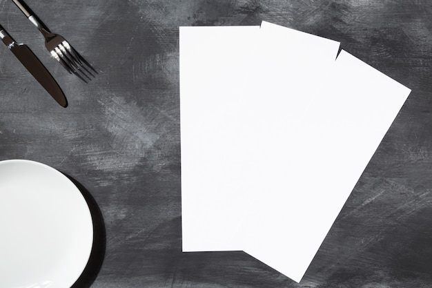 Mockup menu restaurant three narrow pages, fork and knife, empty plate on black background. top view. copy space