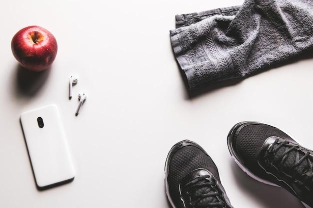 白い背景の上のイヤホンとランニングシューズとモックアップ携帯電話。健康的なアクティブなライフスタイルの背景の概念。毎日のトレーニングと音楽のライフスタイルをリラックスしてください。