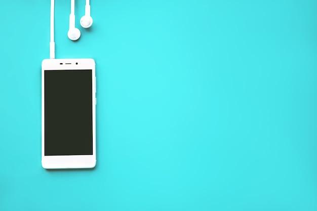 시안색 배경에 헤드폰이 있는 모형 모델 스마트폰.