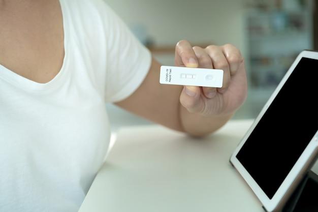 クリッピングパスで分離された空の画面を持つモックアップ現代タブレット。彼女のcovid-19抗原検査結果が陽性だった後、医師とのオンラインビデオ通話にタブレットを使用しているアジアの若い女性。