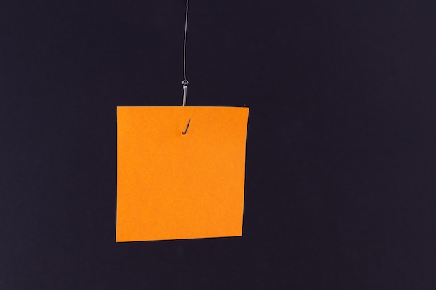 釣り針にぶら下がっているコピースペースと空白のオレンジ色のメモ用紙のモックアップ