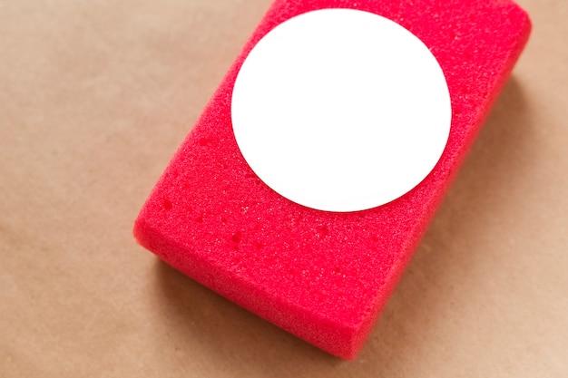 茶色の背景に車を掃除して洗うための赤いスポンジのモックアップ