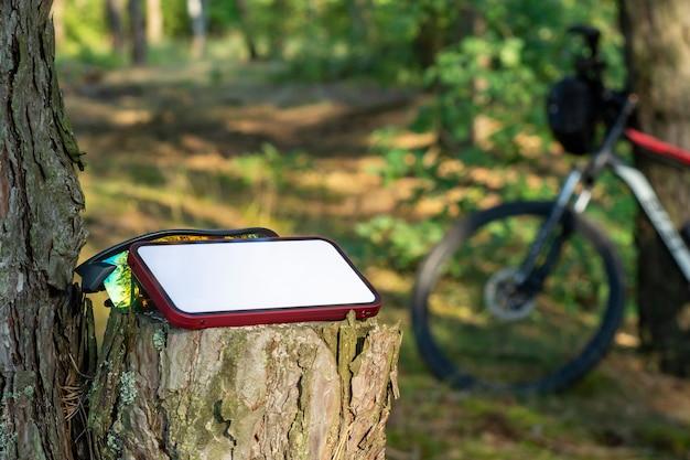 산악 자전거를 배경으로 숲에 흰색 디스플레이가 있는 스마트폰 모형.