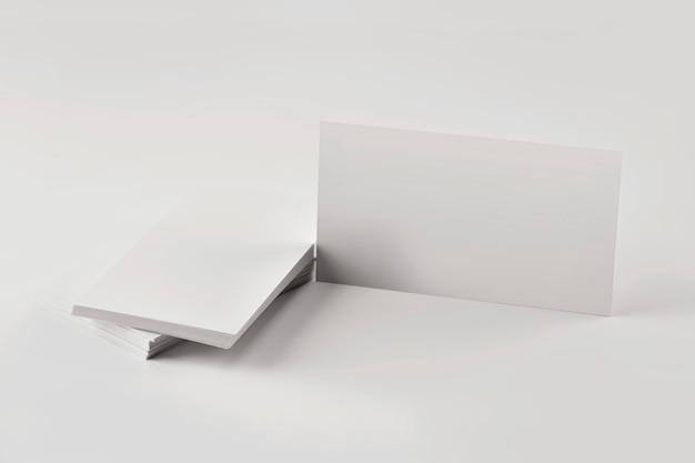 Макет стопки пустых визитных карточек на сером столе крупным планом.