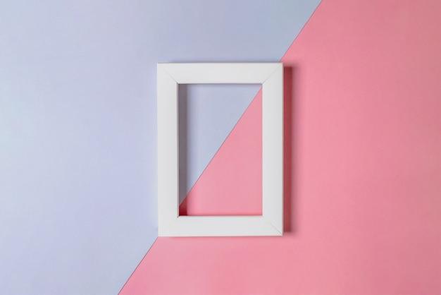 분홍색과 라일락 레이어에 흰색 빈 프레임의 모형. 미니멀리즘. 선택적 초점.