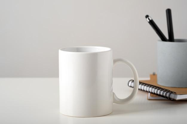 Мокап белой кружки на столе в минималистичном интерьере, деловых канцелярских принадлежностей и блокнотов.