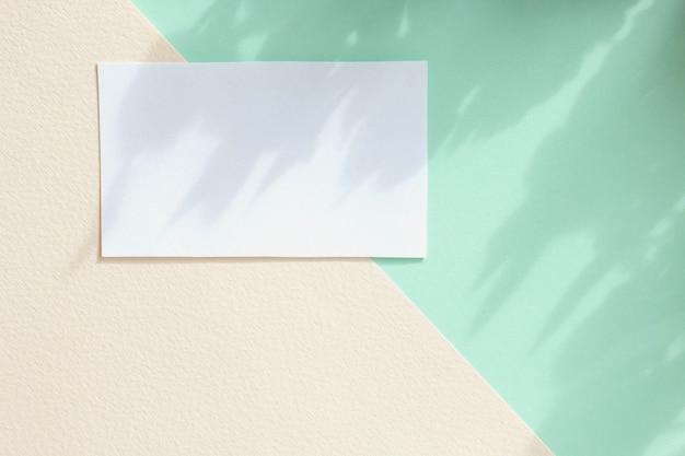 パステル背景、パステル壁紙の創造的なデザインのホワイトペーパーカードのモックアップ。