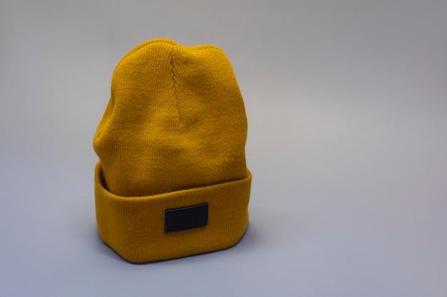 밝은 배경에 주황색 따뜻한 모자의 모형.