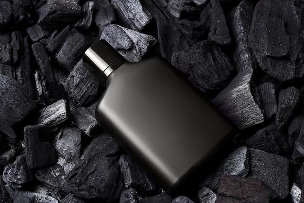 Макет черного парфюмерного макета флакона на темном фоне углей. вид сверху. по горизонтали