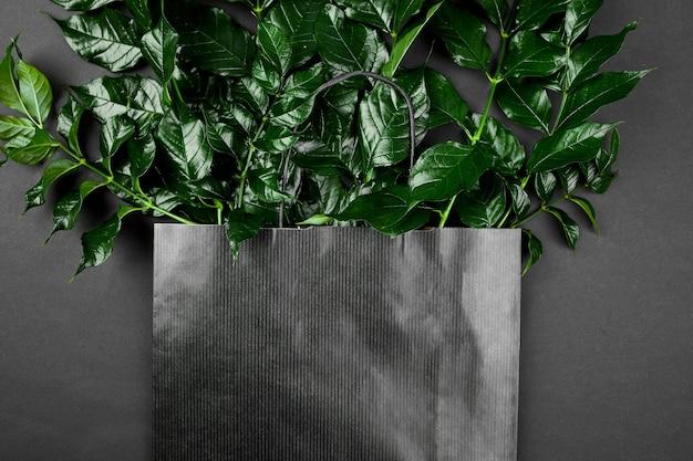 녹색 잎, 평면 평신도, 텍스트를위한 공간, 평면도와 어두운 배경에 검은 쇼핑백의 모형