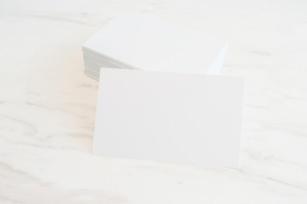 Макет пустых визитных карточек на фоне мраморного стола. шаблон для id. для презентаций и портфолио дизайна.