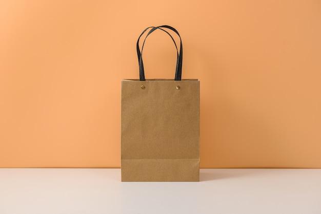 空白のクラフトパッケージのモックアップまたはハンドル付きの茶色の紙のショッピングバッグ