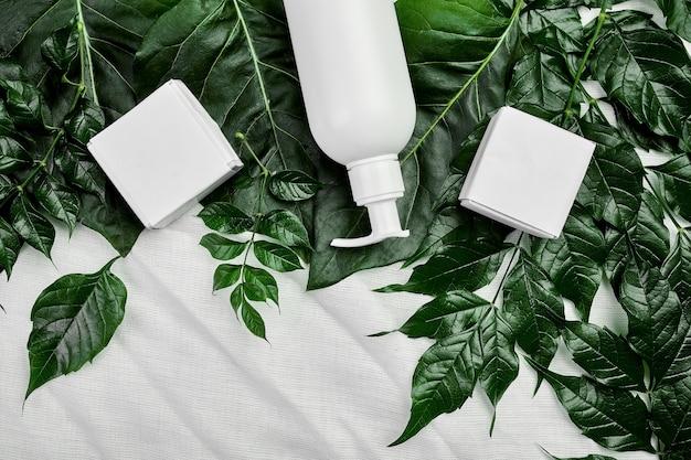 Макет пустой белой бутылки на зеленых тропических листьях, косметическая упаковка, вид сверху кремовой трубки, плоская композиция