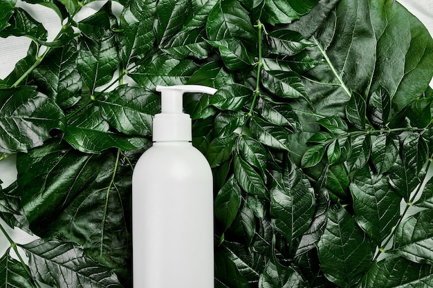 緑の熱帯の葉の上の空白の白いボトルのモックアップ、スパのコンセプト、天然有機化粧品包装プラスチック、クリームチューブトップビュー、フラットレイ構成広告またはバナーテンプレート