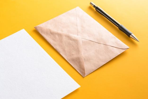 クラフト紙封筒と黄色の背景に鉛筆で空白の白いカードのモックアップ