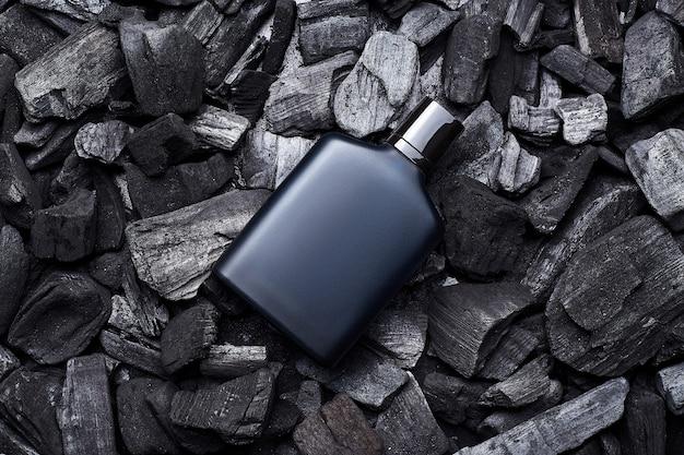 暗い石炭の背景に青い香りの香水瓶のモックアップのモックアップ。上面図。水平