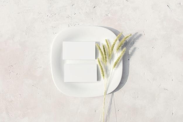 Макет визитных карточек на белой тарелке с сушеным цветком пампасной травы на столе плоская планировка