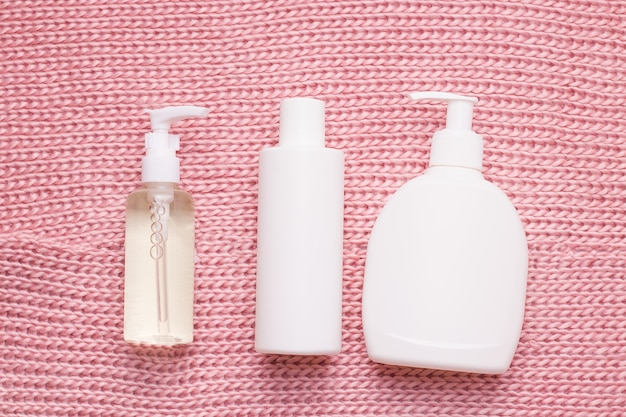 Мокап косметики в белом флаконе на текстуре вязаного, теплого, розового шарфа