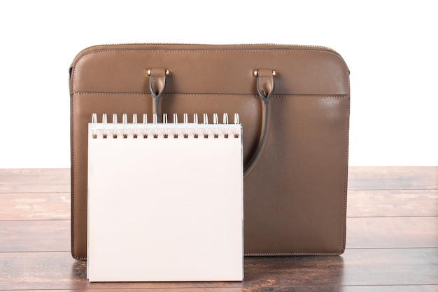 Макет пустого пустого блокнота и портфеля дела, стоящего на столе. изолированные на белом фоне. планирование рабочего дня в офисе