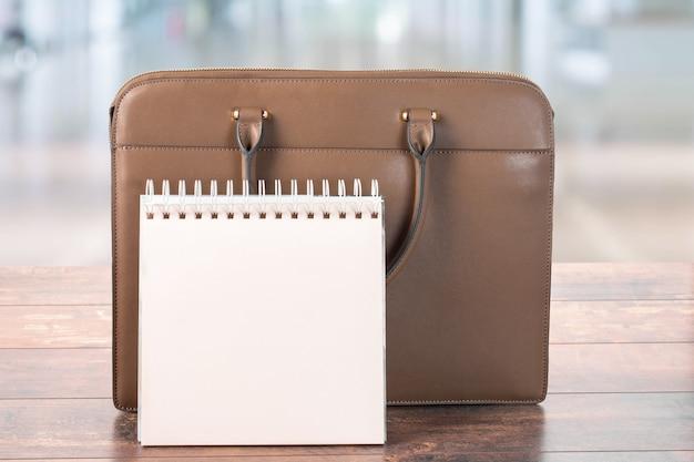 Макет пустого блокнота и портфеля дела, стоящего на столе. на размытом фоне офиса. планирование рабочего дня в офисе