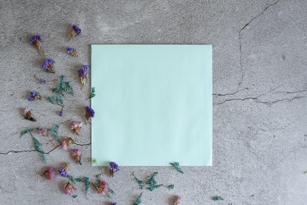 フラットレイアウトスタイルのトップビューの青い背景上の封筒に石膏の花のモックアップ