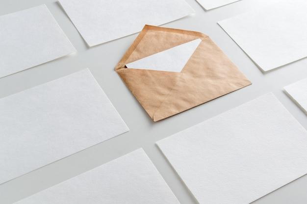 Макет горизонтальных стеков визитных карточек, расположенных в ряд и коричневый конверт в центре