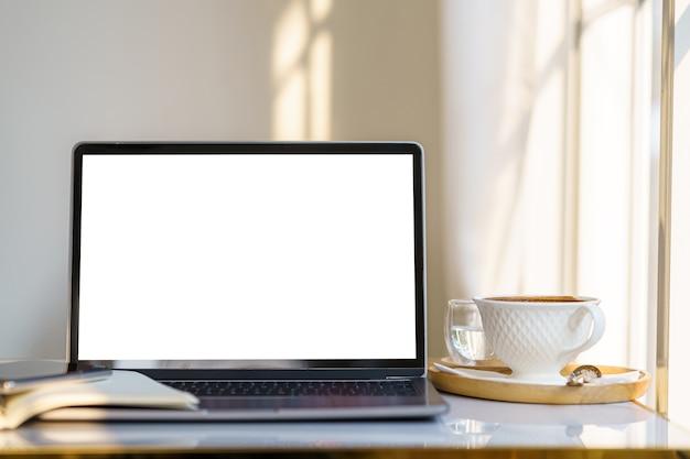 ノートブック、コーヒーカップ、スマートフォンがテーブル側にある空の画面のラップトップコンピューターのモックアップカフェのコーヒーショップの窓、白い画面