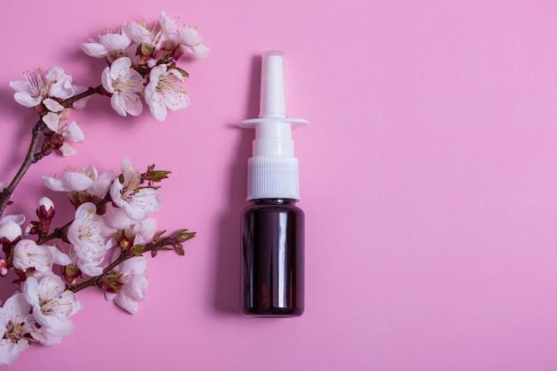 분홍색 배경에 코 스프레이와 꽃이 만발한 나뭇가지를 흉내냅니다. 알레르기 치료제