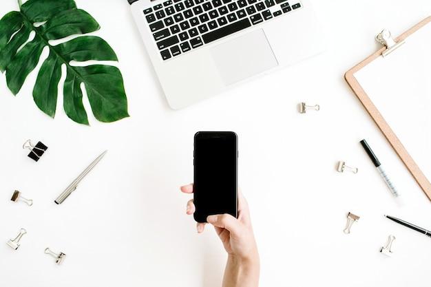女性の手のワークスペースで黒い画面とスマートフォンのモックアップ