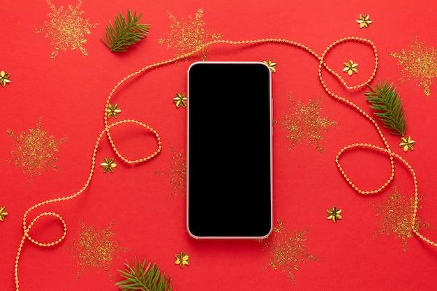 Макет смартфона с черным экраном на украшенном красном новогоднем фоне
