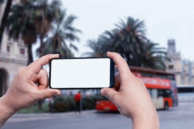 通りで男の手にスマートフォンのモックアップ