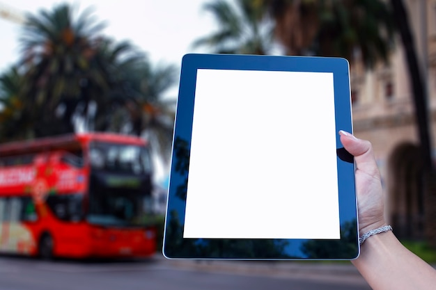 観光バスとヤシの木の背景に白い画面で、女の子の手でタブレットのモックアップ。観光とオンライン旅行。