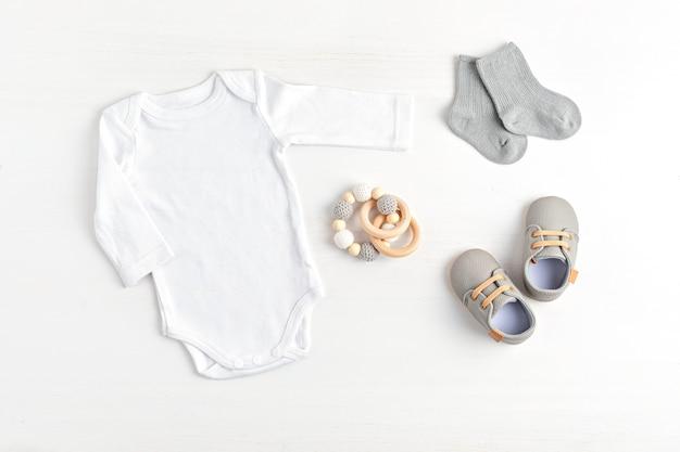 Мокап белого детского боди из натурального хлопка с экологически чистыми детскими аксессуарами. комбинезон для бренда, логотипа, рекламы. плоская планировка, вид сверху