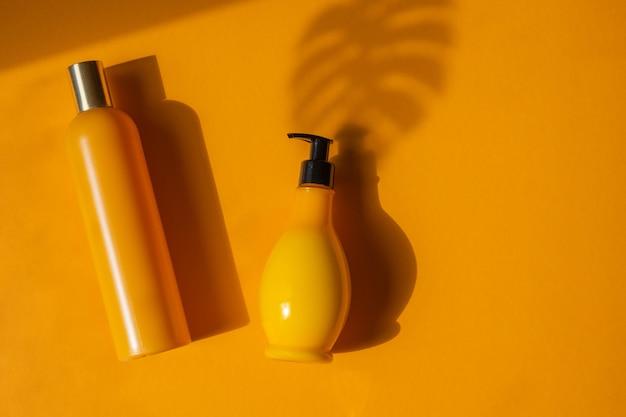 黄色の背景に影のモンステラの葉と黄色の化粧品ボトルのモックアップ。化粧品のクリエイティブでミニマルなショット。夏のコンセプト、ナチュラルコスメ。フラットレイ。