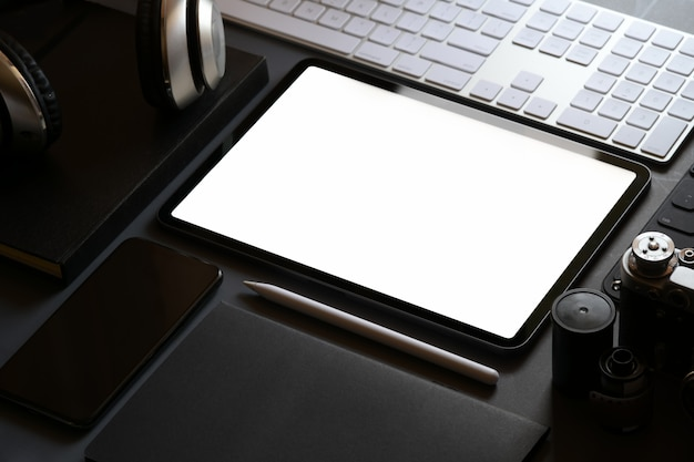 Mockup office stationary with blank screen tablet on dark leather workspace desk
