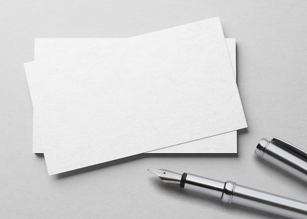 Mockup of one business card  with fountain pen at white textured paper background