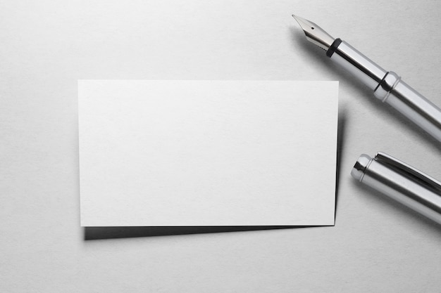 Mockup of one business card  with fountain pen at white textured paper surface
