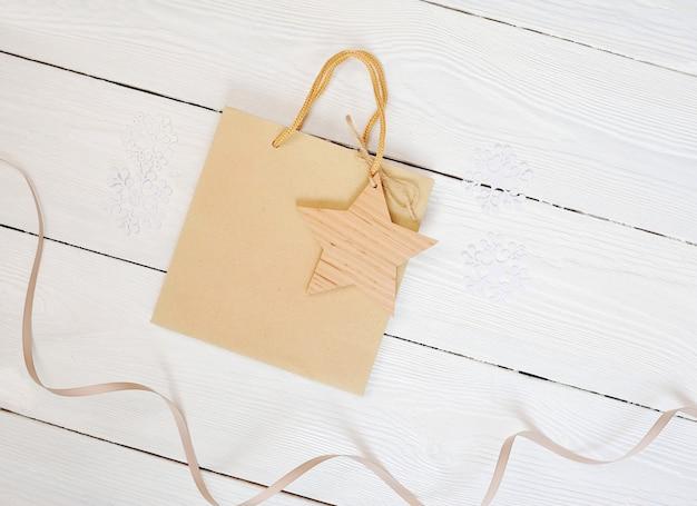 Мокап бумажный пакет из крафт-бумаги со звездой подарочной бирки и на деревянном фоне. плоский макет, вид сверху.
