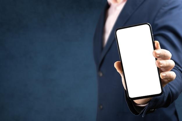 モックアップ電話。ビジネスマンは空白の画面で携帯電話を表示します。オンラインビジネスの概念
