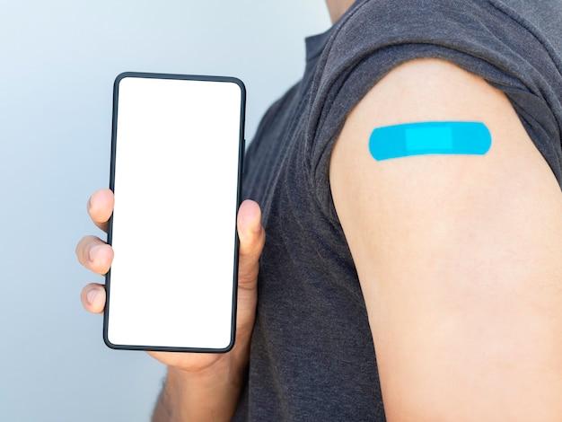 モックアップ電話、医療用フェイスマスクと白い包帯で隔離された肩に青い包帯石膏を身に着けているワクチン接種を受けた男性が示すスマートフォンの白い空白の画面をクローズアップします。