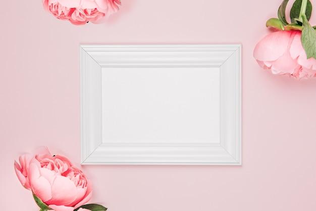 花とピンクの背景にモックアップフォトフレーム。ピンクの牡丹、牡丹のつぼみで繊細でエレガントな背景。フラットレイ、上面図。