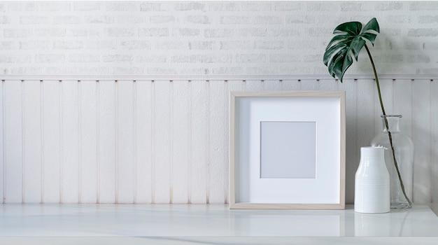 白い部屋の白い大理石のテーブルにモックアップ画像木製フレームとセラミック花瓶