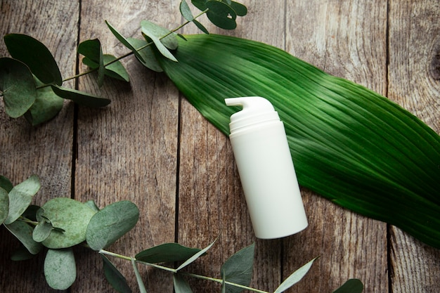 Mockup of plastic packaging and bottles with natural organic cosmetics with leaf